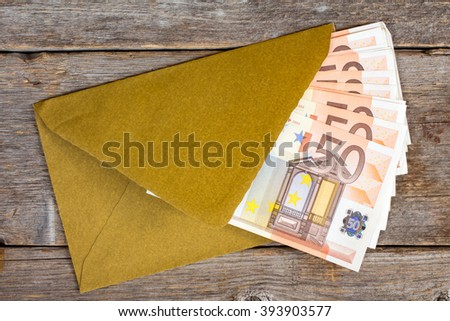 Golden envelope with Euro bills over wooden background - stock photo
