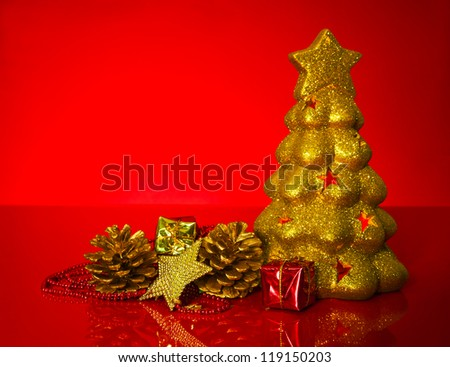 Golden evergreen with Christmas decorations over red background - stock photo