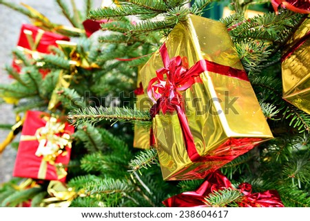 Golden foil gift boxes on street Christmas fir with rain drops - stock photo