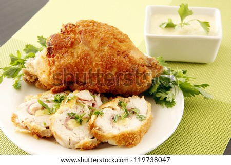 Golden fried stuffed chicken with cream and garnishing - stock photo