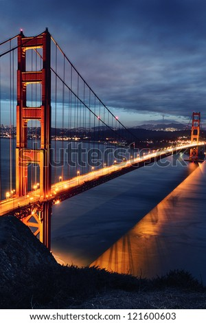 Golden Gate Bridge and San Francisco lights at sunset - stock photo