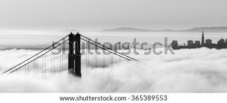 Golden Gate Bridge and skyscrapers are  shown in a fog , San Francisco, California - stock photo