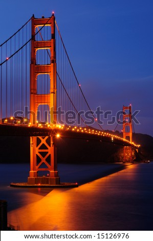 Golden Gate Bridge illuminated at dusk. Shot from a hill over Fort Point, San Francisco, California. - stock photo