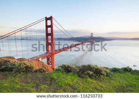 Golden Gate Bridge in clear blue sky with green grass as foreground. San Francisco, USA. - stock photo