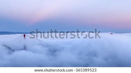 Golden Gate Bridge is shown in a fog at sunrise , San Francisco, California - stock photo