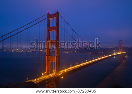 Golden Gate Bridge sunset evening with lights of San Francisco California in background - stock photo