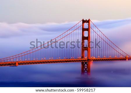 Golden gate in fog at sunset - stock photo