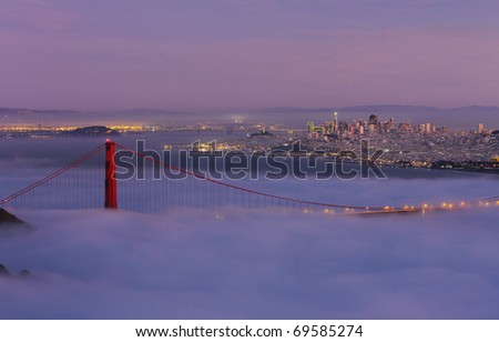 GOLDEN GATE NATIONAL RECREATION AREA, CALIFORNIA: Golden Gate Bridge taken from Hawk Hill overlook in Marin County with fog flowing over bridge at twilight. - stock photo