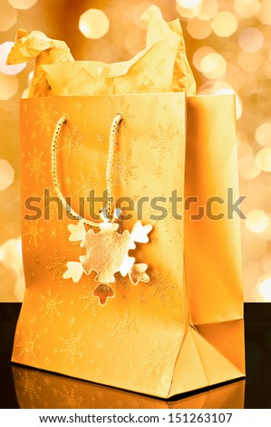 Golden gift bag on golden background - stock photo