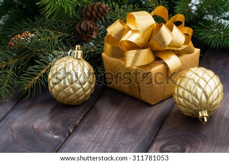 golden gift box and Christmas balls on the background of fir branches, closeup - stock photo