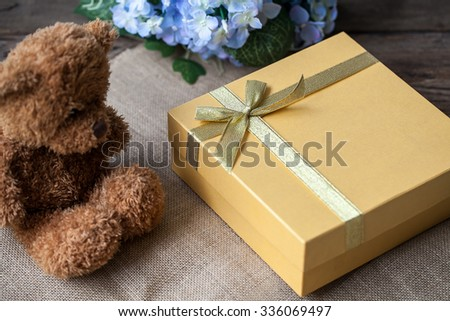 Golden gift box and teddy bear - stock photo