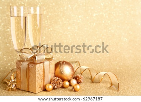 Golden gift box with glasses of champagne - stock photo