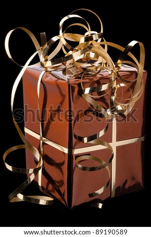 golden gift on a black background - stock photo