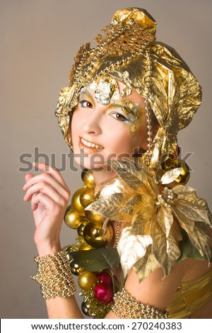 Golden girl. Young woman posing in holiday artistic image with New Year decoration. - stock photo