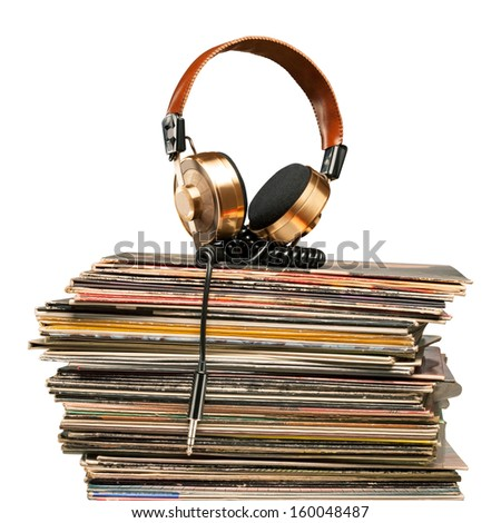 Golden headphones lying on the stack of vinyle records. - stock photo