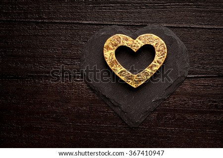 Golden heart on dark wooden background - stock photo