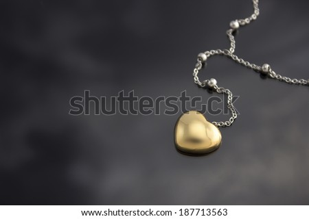 Golden heart with necklace chain on black  background. - stock photo