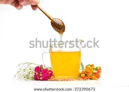 golden honey and colorful flowers, studio shot - stock photo