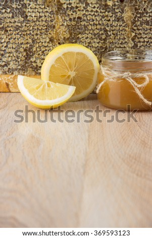 Golden honey in the comb in a jar and yellow lemon - stock photo