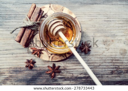 Golden honey with honeystick. cinnamon and anise stars on wooden table - stock photo