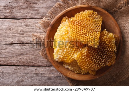 Golden honeycomb on a wooden plate on the table. horizontal view from above
