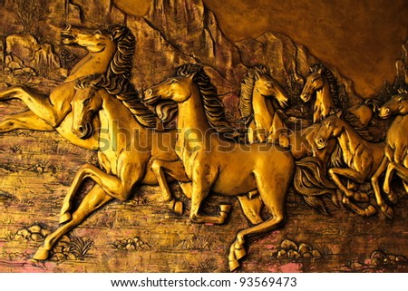 Golden Horses sculptures on the wall - stock photo