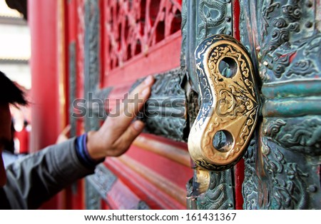 Golden key in the door of a Chinese temple.  The believer touches the sacred door of Chinese temple according to ancient tradition. Canon 5D. - stock photo
