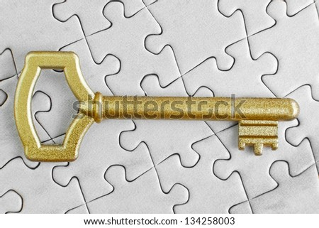 Golden Key to the puzzle close-up. - stock photo