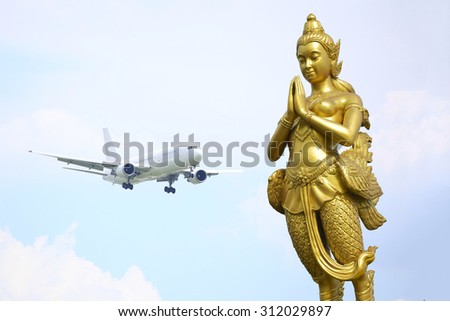 Golden kinnaree statue, a half woman at passenger plane fly up over take-off runway from airport  - stock photo