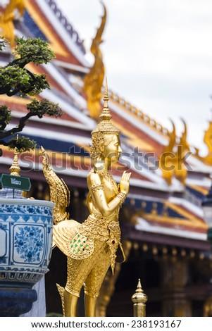 Golden Kinnari statue at Temple of Emerald Buddha (Wat Phra Kaew) in Grand Royal Palace. Half-bird, half-woman creature at south-east Asian Buddhist mythology. Bangkok, Thailand - stock photo