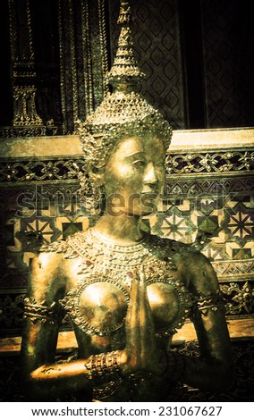 Golden Kinnari statue at the Temple of the Emerald Buddha (Wat Phra Kaew) in Grand Palace complex. (Bangkok, Thailand) Retro aged photo with scratches. - stock photo