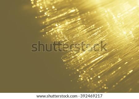 golden light fiber optic, high speed technology of digital telecommunication. - stock photo