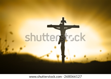 Golden light. Silhouette Jesus and the cross over blurred beautiful sunset background. - stock photo