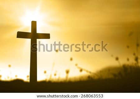 Golden light. Silhouette the cross over blurred beautiful sunset background. - stock photo