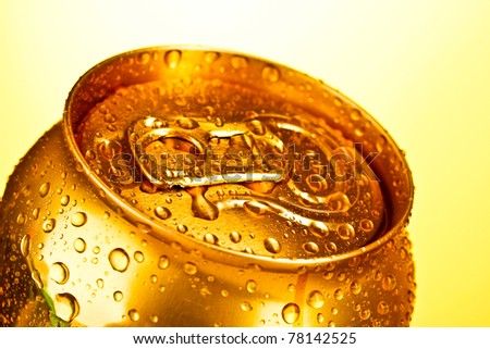 Golden metallic beer with water drops on yellow background - stock photo
