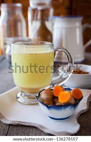 Golden milk. Turmeric herbal medicine, an anti-inflammatory. Shallow DOF, focus on the brim of the glass and the foam on milk - stock photo