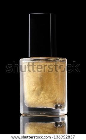 Golden nail polish on black background - stock photo