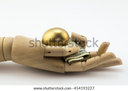 Golden nest egg in palm of wooden hand with dollar notes isolated on white - stock photo
