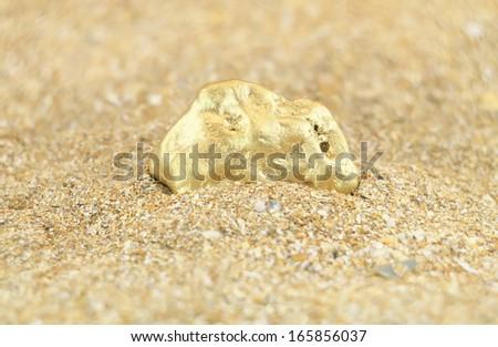 golden nugget treasure in sand - stock photo