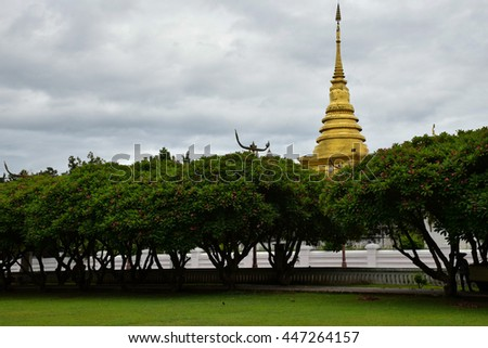 golden pagoda behind the trees in temple at Nan, northern of Thailand, white sky, cloudy   - stock photo