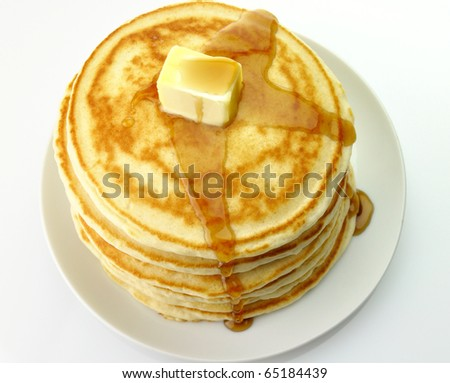 Golden pancakes with butter and maple syrup. - stock photo