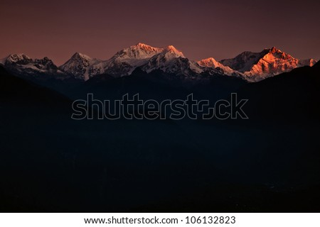 Golden peaks of Mount Kanchendzonga range of the himalayas at first light of dawn - stock photo