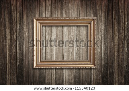 Golden picture frame on wood background - stock photo