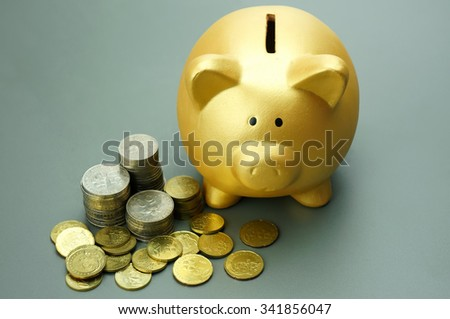 Golden piggy bank and pile of coins - stock photo
