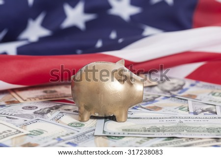 Golden Piggy Bank on Dollars with American Flag - stock photo