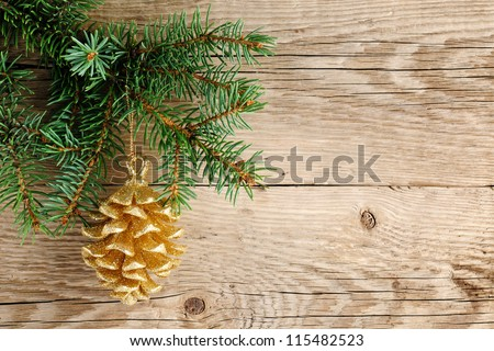 Golden pine cone on christmas tree - stock photo