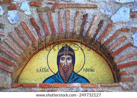 Golden portrait of Osiou Louka saint above monastery gate (UNESCO world heritage list), 8th of May 2014, Greece - stock photo