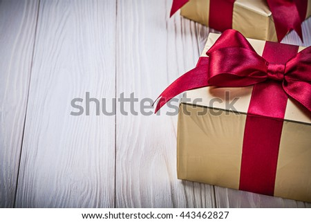 Golden present boxes with tied bows on wooden board holidays concept. - stock photo