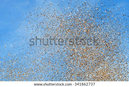 golden rain of the golden confetti in the city festival on blue sky background  - stock photo