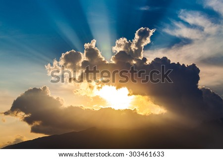 golden rays of the sun through the black clouds - stock photo